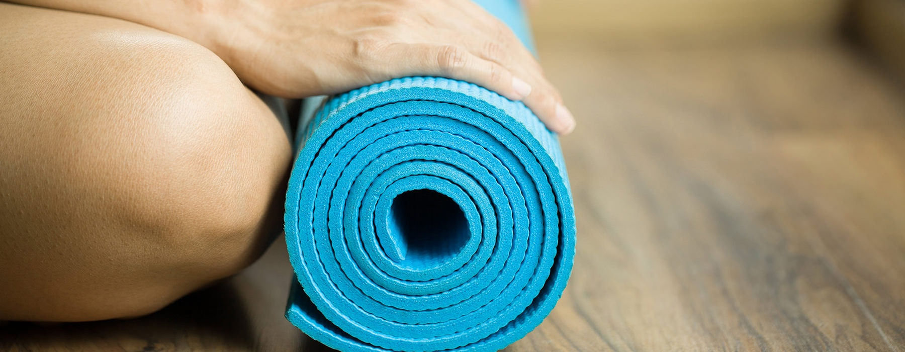 bright blue yoga mat in a roll on the floor