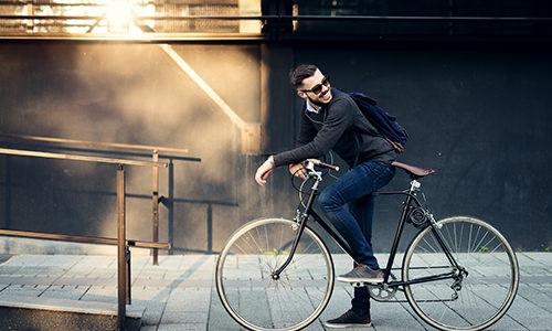A man sitting on a bike on a sidewalk